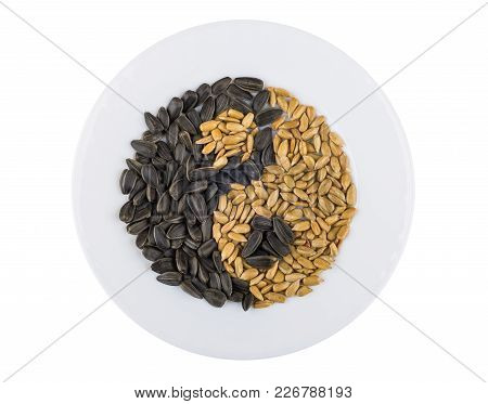 Plate With Fried Peeled And Unpeeled Sunflower Seeds In Form Yin-yang Isolated On White Background.