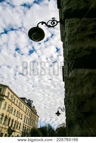 Old Balconies Street Lamp On Stone Wall At Foreground Against Blue Sky With White Clouds In Centenar
