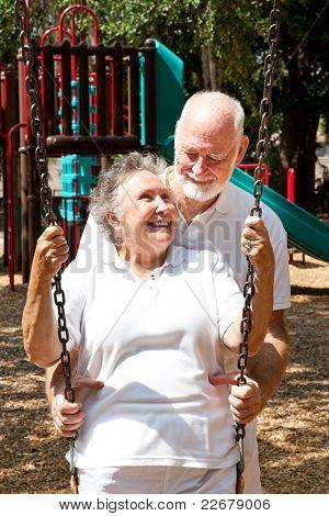 Senior couple on a playground, swinging on the swingset.