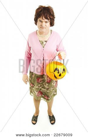 Embarassed father dressed up as a woman on Halloween, carrying a pumpkin bucket of candy.  Full body isolated on white.
