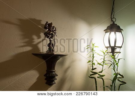 The Statuette Of God Ganesha In The Light Of A Lamp