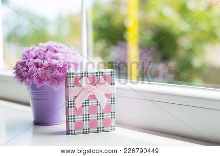 Little Purple Bucket With Tender Bouquet Of Beautiful Pink Carnation With Gift Box Near Window In Da
