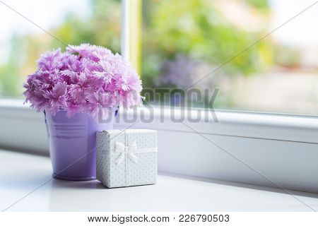 Little Purple Bucket With Tender Bouquet Of Beautiful Pink Carnation With White Gift Box Near Window