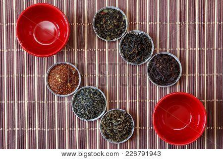 Ivan Tea, Rooibos Marrakech, Black Tea, Green Tea And Red Cups On A Brown Bamboo Mat, Top View Close