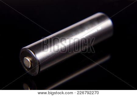 Black Aa Battery On The Dark Reflective Background