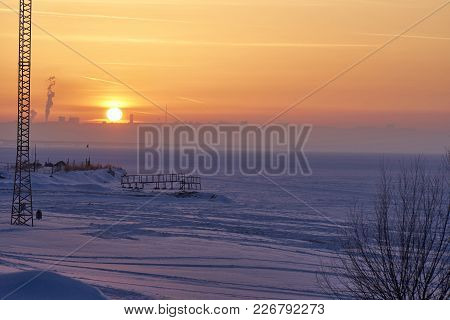 A Winter Sunset Over A Large Frozen Lake. On The Far Bank In The Haze Are Visible Silhouettes Of Bui