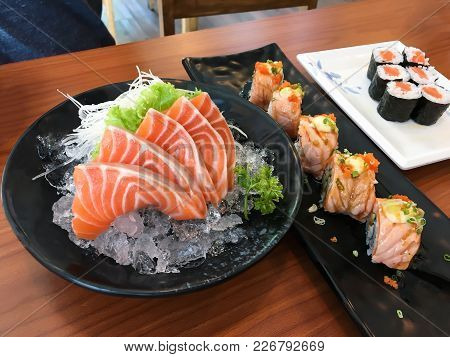 Salmon Raw Sashimi In Black Brown With Sushi Rolls On Wood Table.