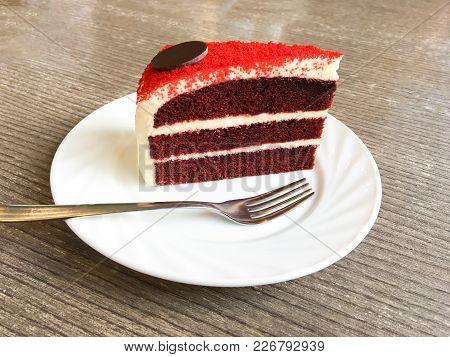Tasty Red Velvet Cake With Fork On Table At Cafe.