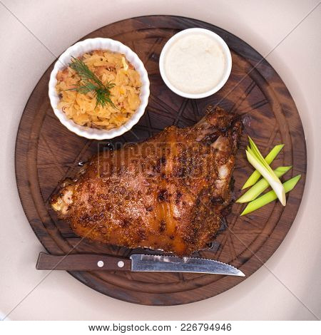 Restaurant dish - a large baked pork knuckle on a wooden tray