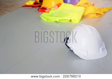 Close Up White Safety Helmet With Reflective Clothing Conference Table At Construction Site And Scaf