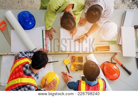 Top View Of Group Of Engineer, Technician And Architect Planning About Building Plan With Blueprint