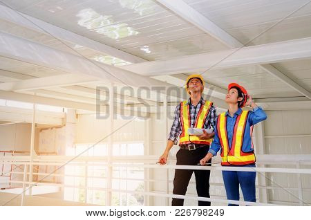 Couple Of Engineer Or Technician Man And Woman With Safety Helmet Holding Blueprint In Construction