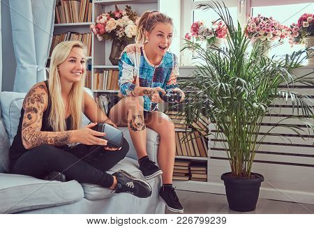 Two Young Girlfriends In Casual Clothes Play Video Games At Home.