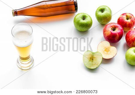 Apple Cider Poured Into Glass Near Bottle And Apples. White Background Top View.