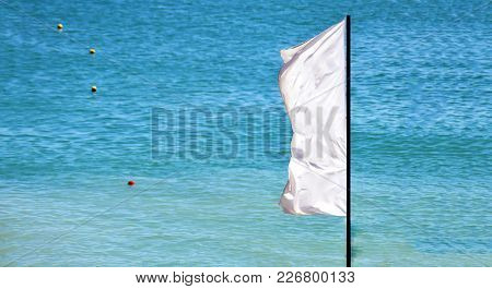 A Waving White Flag With A Blue Sea And Signaling Buoys In The Background
