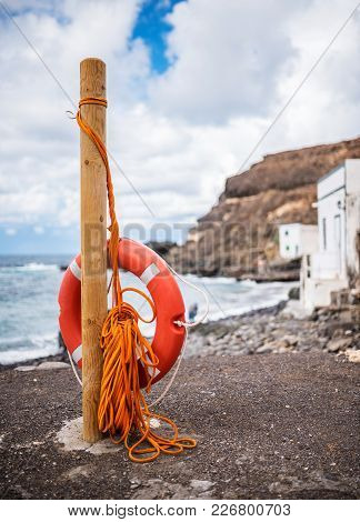 Typical Red Lifebuoy With Rope On Pole With Coast And Ocean In Background