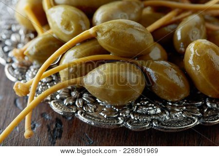 Pickled Caper Berries In Metal Dish .