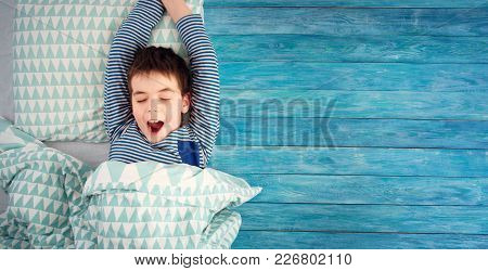 Eight Years Old Child Sleeping In Bed On Pillow. Boy Yawning On Blue Wooden Background