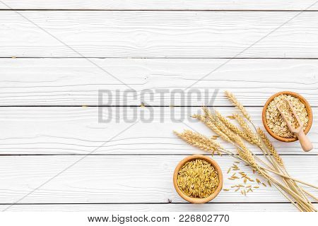 Food Which Rich With Slow Carbohydrates. Oatmeal And Oat In Bowls Near Sprigs Of Wheat On White Wood