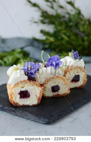 French Eclair With Fruit And Coconut Cream And Gentle Mousse. Delicious Dessert. Cake In The Glaze.