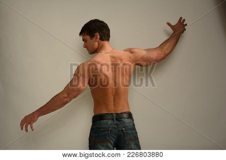 The Photo Shows A Man Stretching His Arms Out.