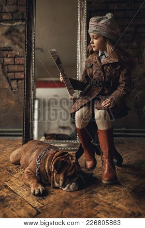 Child Girl In Image Of Sherlock Holmes Sits Next To English Bulldog And Reads Newspaper On Backgroun