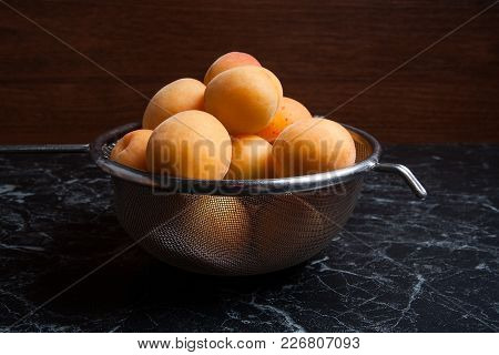 Several Of Harvested Apricots Whole And Halved In Steel Colander..