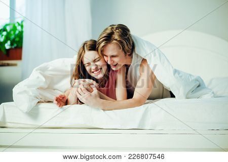 Cheerful Pair Of Lovers Still In Bed. A Boy Is Holding His Princess.