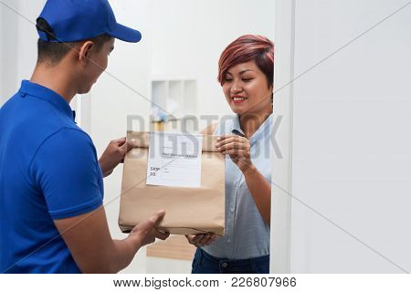 Fast Delivery Service Manager Bringing Package To Female Client