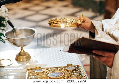Oath At The Newlyweds On Luxuriously Decorated Bible, Hands Of Men And Women In Church Near The Alta