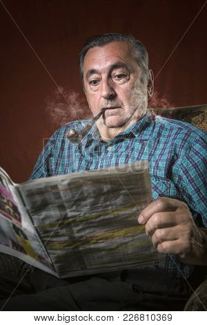 Senior Old Man Shocked With News In The Papers, Smoking A Pipe