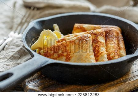 Delicious Crepes With Butter In A Cast Iron Pan.