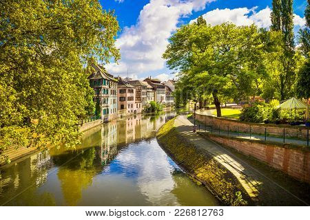 Strasbourg, Water Canal In Petite France Area. Half Timbered Houses And Trees In Grand Ile. Alsace,