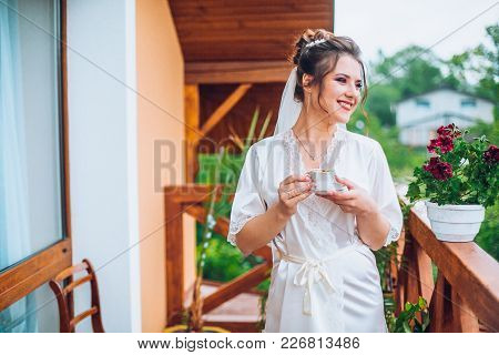 Gorgeous Bride In Elegant Robe Drinking Coffee In Luxury Hotel Balcony Near Window, Morning Before T