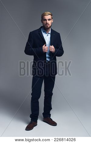 Successful And Handsome. Young Business Man Holding Lapels Standing In Front Of Grey Background