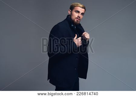 Young And Handsome. Attractive Business Man Holding Lapels Standing In Front Of Grey Backgound