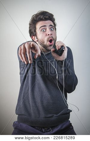 Young Man Dancing And Singing To The Music On His Mobile Phone Through Earphones, Goofy And Happy