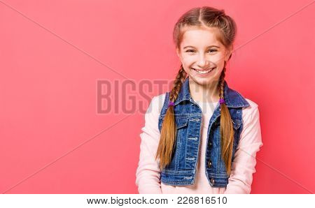 Smiling teen girl with two french braid in casual clothes posing over pink background