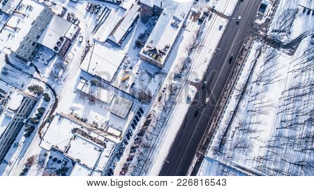 Aerial view on city in winter day. City panorama with straight road covered with snow from a bird eye view