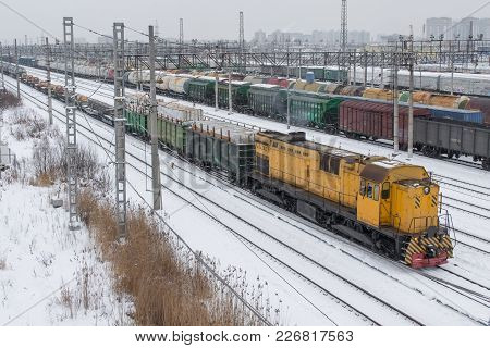 Freight Train To The Marshalling Yard In Winter In The Snow. Yellow Locomotive
