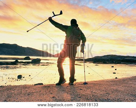 Disabled Man With Prosthesis And Crutches Near Sea Holding Hand In The Air.  Evening Sun At Rocky Ho