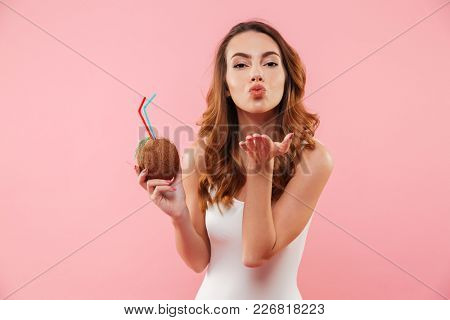Slim brunette woman in white swimsuit enjoying summertime with coconut drink in hands and blowing air kiss on camera, isolated over pink background