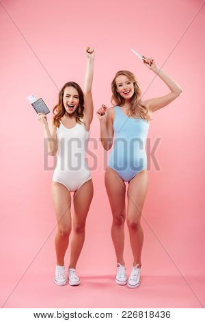 Full length portrait of a two excited girls dressed in swimsuits holding passports with flying tickets and celebrating isolated over pink background