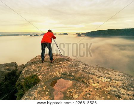 Photo Artist In Work. Photographer In Rocky Mountains. Traveller Takes Photos Of Dreamy Majestic Lan