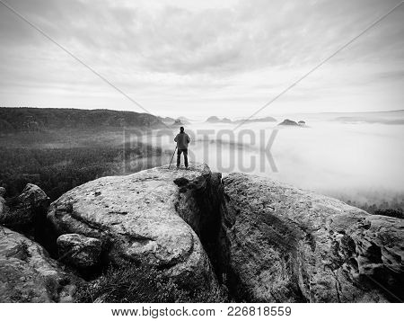 Artist Photographer Works With Tripod On Cliff Above Clouds. Dreamy Fogy Landscape, Misty Sunrise In