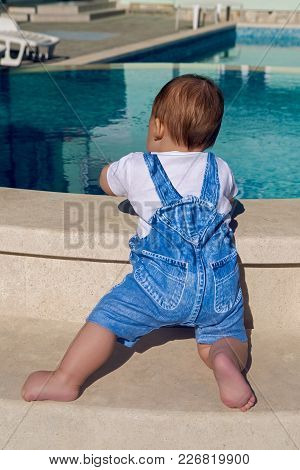 Child In A Denim Suit Sits On The Edge Of The Pool