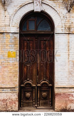 The Facade Of An Ancient Building With An Old Double-leafed Brown Wooden Door Decorated With Volumin