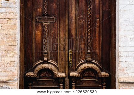 Vintage Background. Brass-made Old Handle With Elements Of An Carved Wooden Door Decorated With Mass