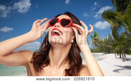 valentines day, beauty and people concept - happy smiling young woman with red lipstick and heart shaped sunglasses over exotic tropical beach with palm trees background