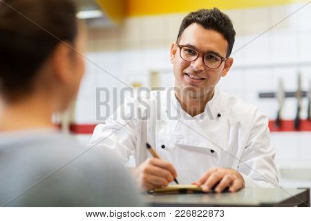 people, fast food and cooking concept - happy smiling chef at restaurant writing order and customer